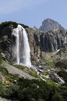 Foto vertical de uma cachoeira na passagem de susten localizada na suíça no inverno durante o dia