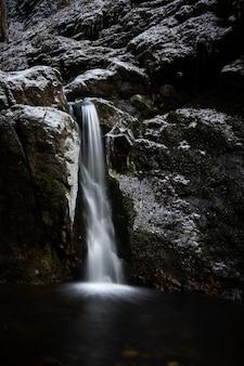 Foto vertical de uma cachoeira saindo de uma enorme rocha coberta de neve no inverno