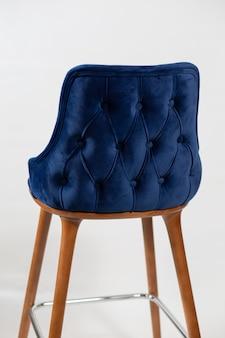 Foto vertical de uma cadeira azul com botões atrás de um fundo branco