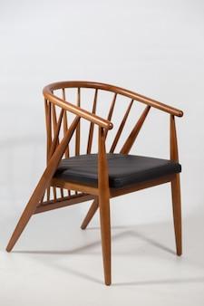 Foto vertical de uma cadeira de madeira atrás de um branco