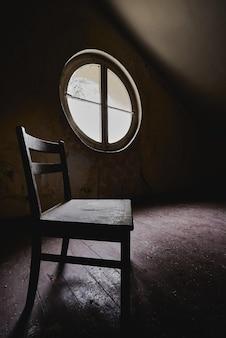 Foto vertical de uma cadeira de madeira em um quarto escuro com uma janela redonda - conceito de isolamento