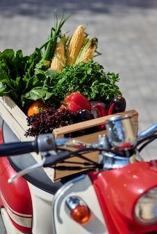 Foto vertical de uma caixa de madeira com legumes frescos em uma scooter em pé na cidade