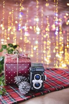 Foto vertical de uma câmera vintage com uma caixa de presente em uma toalha de mesa listrada com luzes de natal