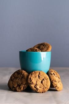 Foto vertical de uma caneca azul de leite e biscoitos de chocolate ao redor