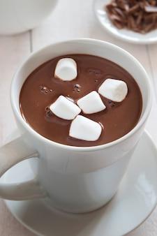 Foto vertical de uma caneca branca de chocolate quente com marshmallow