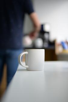 Foto vertical de uma caneca de café branca sobre a mesa