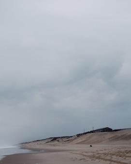 Foto vertical de uma casa solitária na praia sob um céu nublado