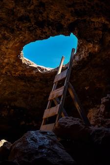 Foto vertical de uma caverna rochosa com um grande buraco e uma escada de madeira - perfeito para o conceito de minas antigas