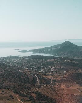Foto vertical de uma cidade e uma montanha perto da praia em uma das ilhas gregas