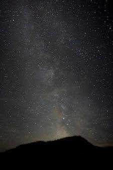 Foto vertical de uma colina com uma paisagem deslumbrante da via láctea