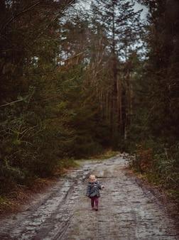 Foto vertical de uma criança caminhando em uma estrada lamacenta cercada por árvores