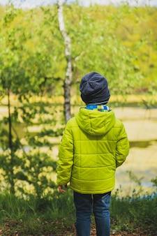 Foto vertical de uma criança com um casaco amarelo brincando no parquinho