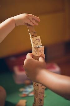 Foto vertical de uma criança e um adulto brincando com cubos de madeira educacionais no chão