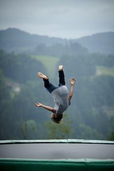 Foto vertical de uma criança pulando em um trampolim com montanhas