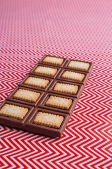 Foto vertical de uma deliciosa barra de chocolate com visão de ângulo de biscoitos crocantes