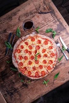 Foto vertical de uma deliciosa pizza de pepperoni com queijo com uma taça de vinho em uma mesa de madeira