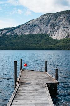 Foto vertical de uma doca de madeira perto do lago com altas montanhas rochosas
