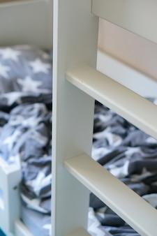 Foto vertical de uma escada de madeira branca perto da cama
