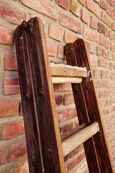 Foto vertical de uma escada dobrável de madeira apoiada em uma parede de tijolos