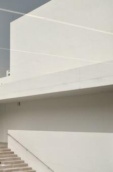 Foto vertical de uma escada próxima a uma parede branca