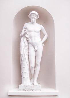Foto vertical de uma escultura em pedra branca de um homem nu