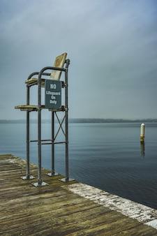 Foto vertical de uma estação de salva-vidas na doca com um mar aberto e um céu escuro ao fundo