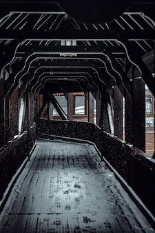 Foto vertical de uma estrada de madeira que leva ao trem coberto de neve