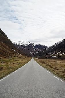 Foto vertical de uma estrada levando a belas montanhas nevadas