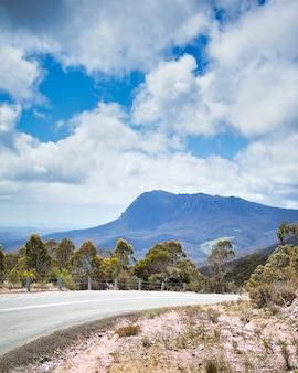Foto vertical de uma estrada panorâmica desaparecendo no horizonte com uma montanha ao fundo