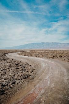 Foto vertical de uma estrada sinuosa cercada por um terreno arenoso