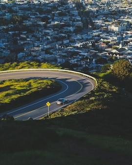 Foto vertical de uma estrada sinuosa descendo a colina com prédios à distância