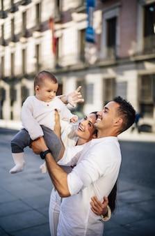 Foto vertical de uma família feliz segurando seu filho bebê