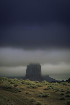 Foto vertical de uma formação rochosa no meio de um cenário deserto coberto de névoa