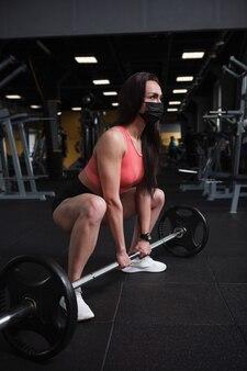 Foto vertical de uma forte atleta levantando barra em um agachamento de sumô