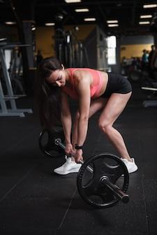 Foto vertical de uma forte desportista a preparar-se para treinar com barra