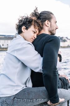 Foto vertical de uma garota abraçando seu parceiro de volta com o mar fora de foco