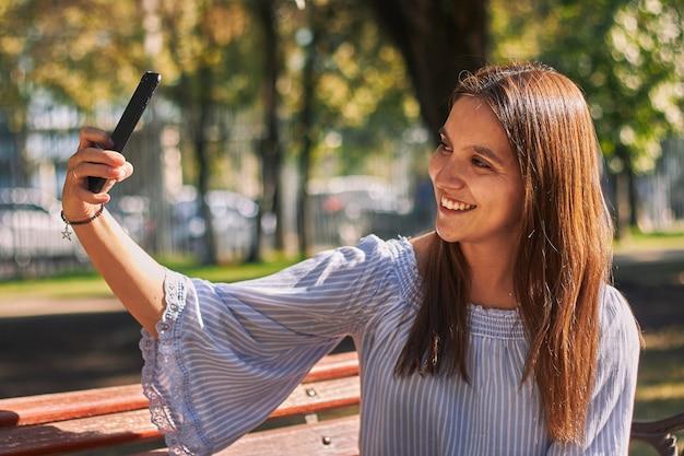 Foto vertical de uma garota com uma camisa azul tirando uma selfie