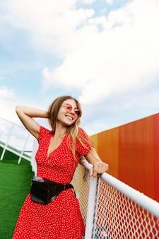 Foto vertical de uma garota loira e bonita com vestido de verão e óculos de sol vermelhos, apoiando-se no corrimão no parque.