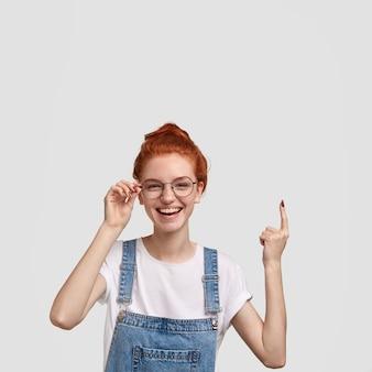 Foto vertical de uma garota sorridente feliz e sardenta com cabelo ruivo, aponta com o dedo indicador para cima, mostra espaço livre para seu anúncio, mantém a mão na borda dos óculos, expressa felicidade
