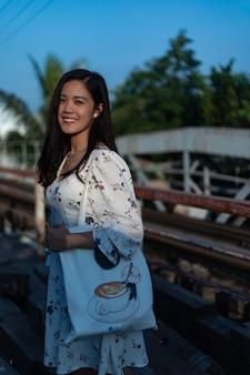 Foto vertical de uma garota vietnamita em uma ponte velha