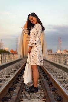 Foto vertical de uma garota vietnamita parada nos trilhos de um trem em uma ponte velha
