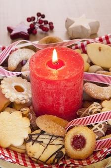 Foto vertical de uma grande vela vermelha acesa com biscoitos e enfeites de natal