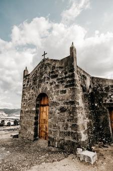 Foto vertical de uma igreja antiga com porta de madeira e paredes em ruínas durante o dia
