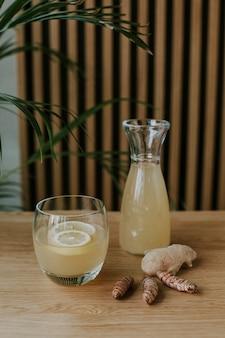 Foto vertical de uma jarra e um copo cheio de limonada e um par de gengibre em uma mesa de madeira