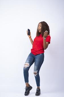 Foto vertical de uma jovem africana animada segurando o telefone, olhando feliz para o lado dela