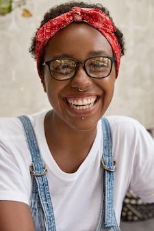 Foto vertical de uma jovem afro-americana feliz e alegre com um sorriso cheio de dentes
