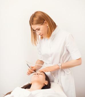 Foto vertical de uma jovem apreciando o procedimento de dermoabrasão.