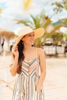Foto vertical de uma jovem de férias na praia.