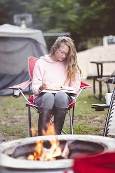 Foto vertical de uma jovem estudando ao ar livre em frente a uma fogueira