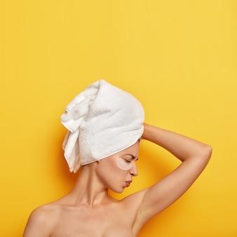 Foto vertical de uma jovem insatisfeita com um cheiro desagradável de suor embaixo da axila, franze a testa em insatisfação e usa uma toalha branca
